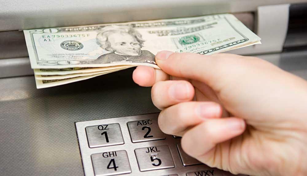 Hand inserting us $20 bills into Broadway Bank ATM