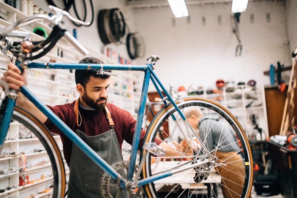 Bike shop owner working on vintage bicycle