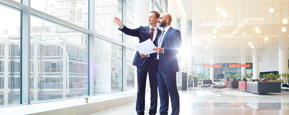 Businessmen standing in corporate lobby discussing plans