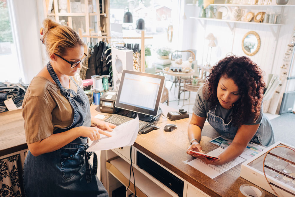 Small business owners reviewing payments together