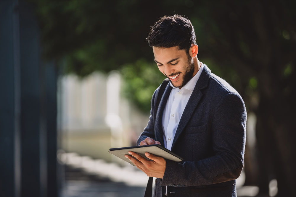 Business man outside reviewing tablet