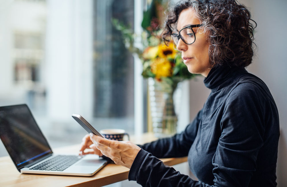 Business woman sitting at office desk reviewing phone while on laptop