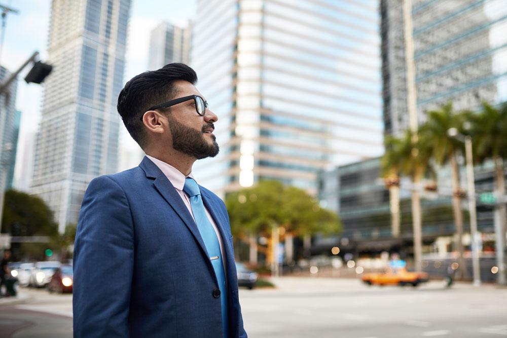businessman walking outside in city landscape