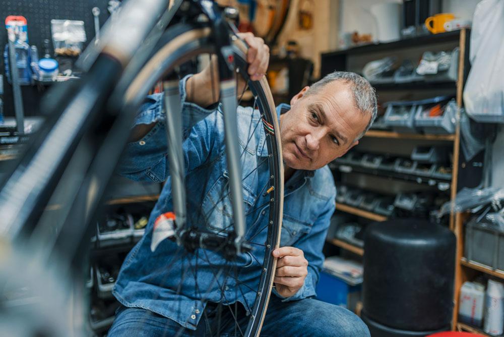 Businessman in his shop repairing a bike