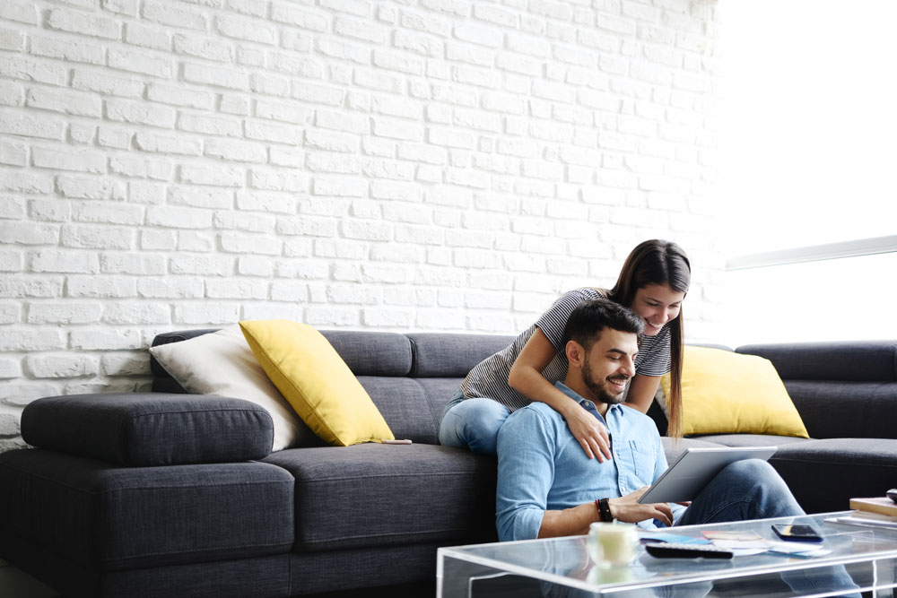 Couple sitting together on their couch reviewing computer