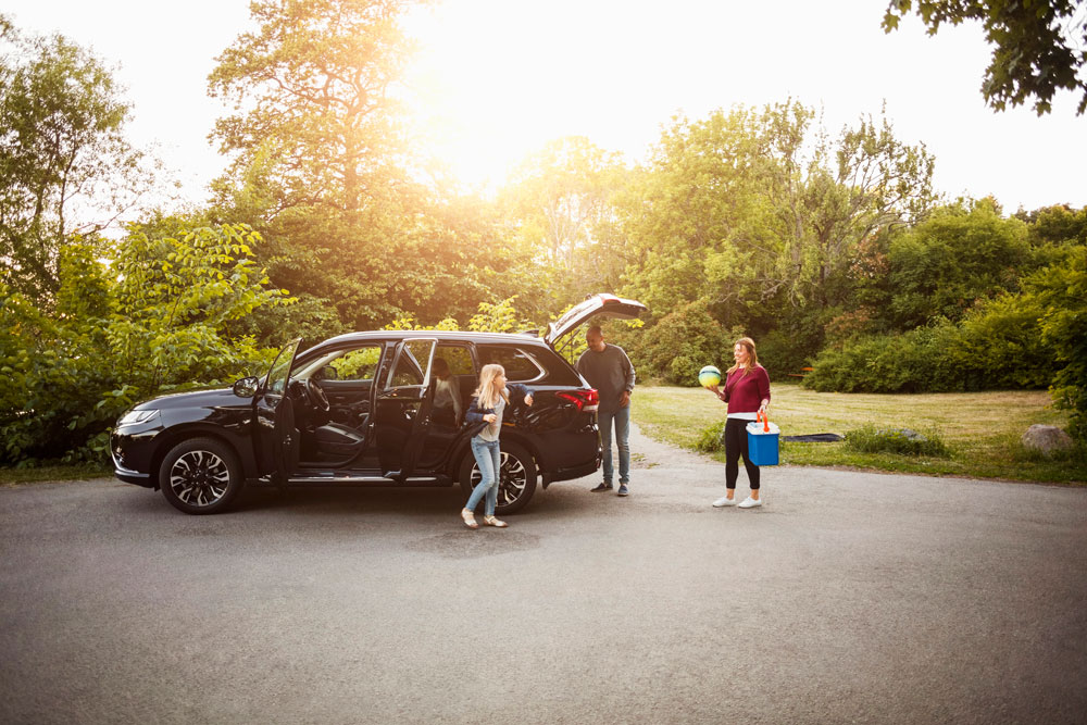 a family celebrates getting their new car by taking it to the park