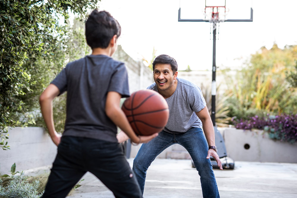 Hispanic father and son playing basketball in the backyard