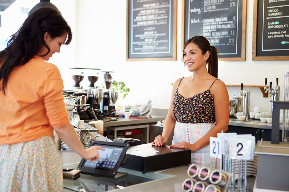 Female coffee shop owner helping customer at front counter