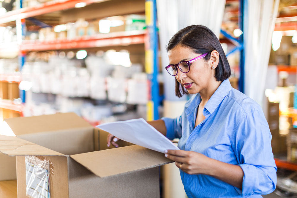 Female business owner reviewing delivery invoice