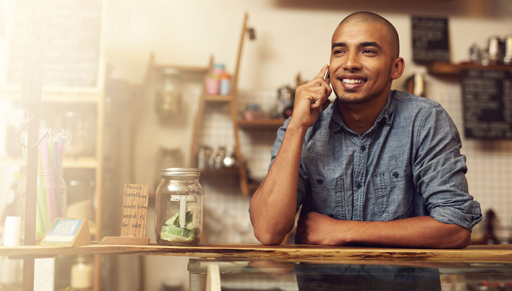 Hispanic male business owner on the phone with customer service