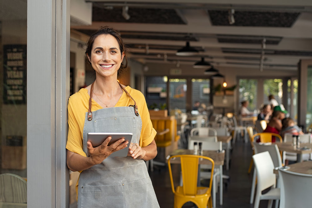 Hispanic woman who owns a restaurant looking at her iPad