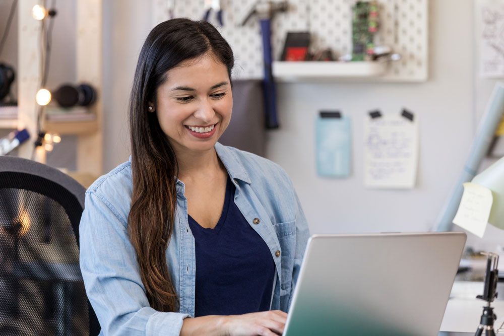 Hispanic small business owner reviewing her business accounts on her laptop