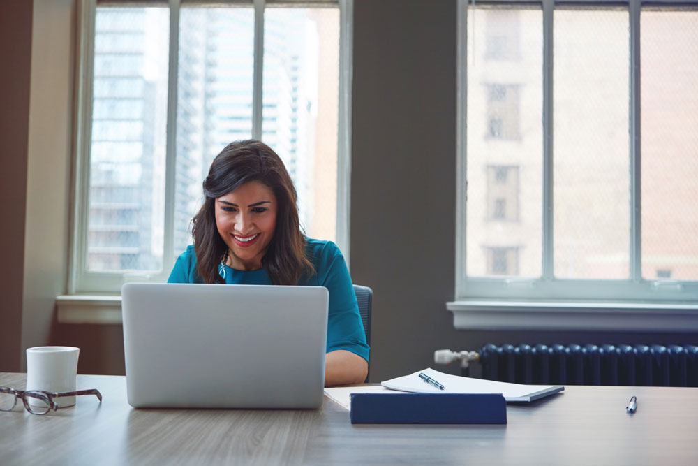 Hispanic business owner sitting at computer reviewing her wire transfers