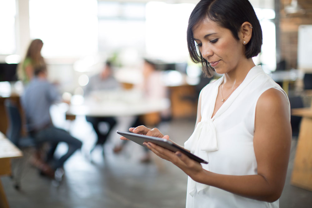 Hispanic business woman reviewing tablet