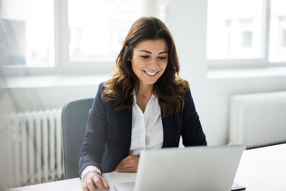 Hispanic business woman sitting at desk reviewing her automated wire transfers