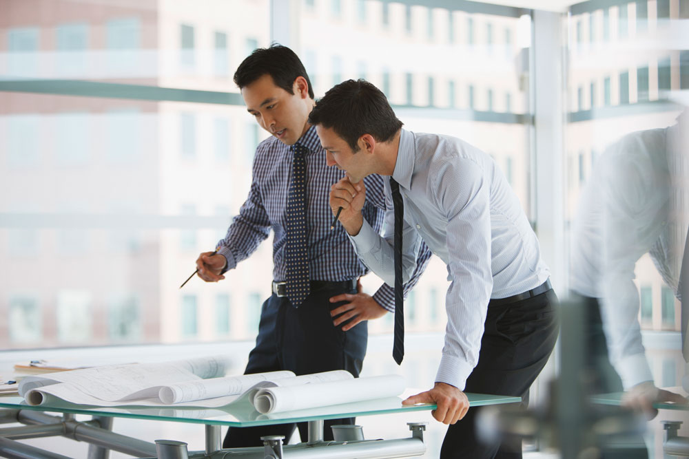 Male coworkers reviewing project together in office setting