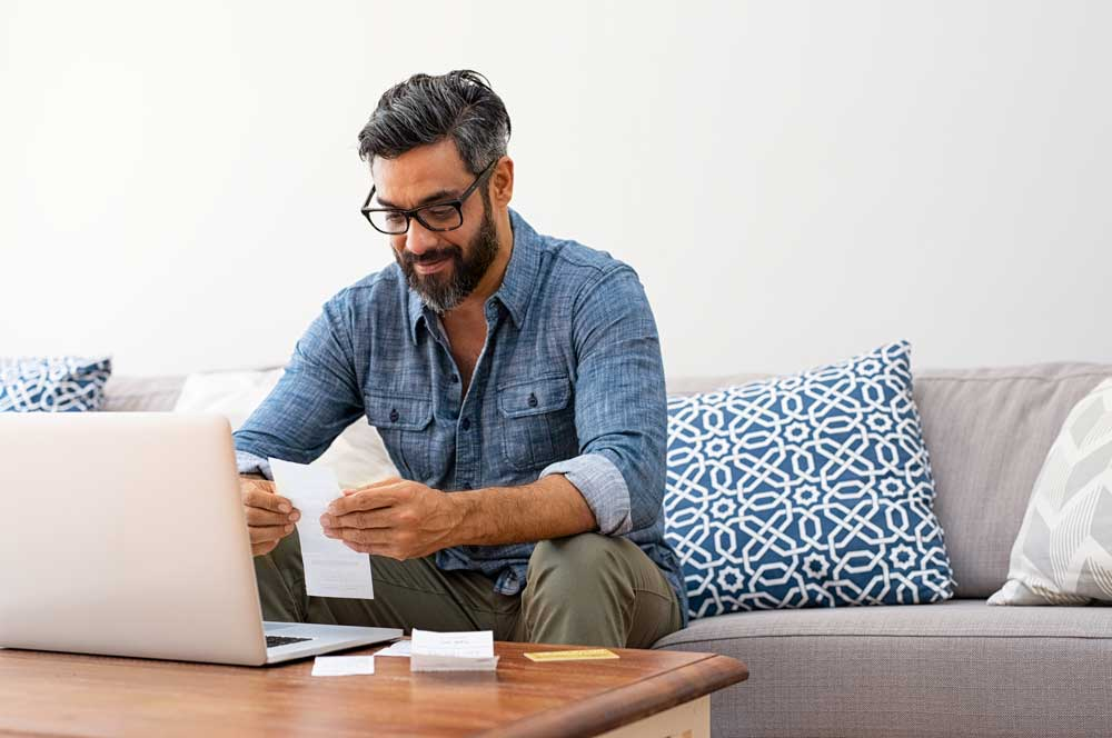 Man sitting in living room at computer paying bills