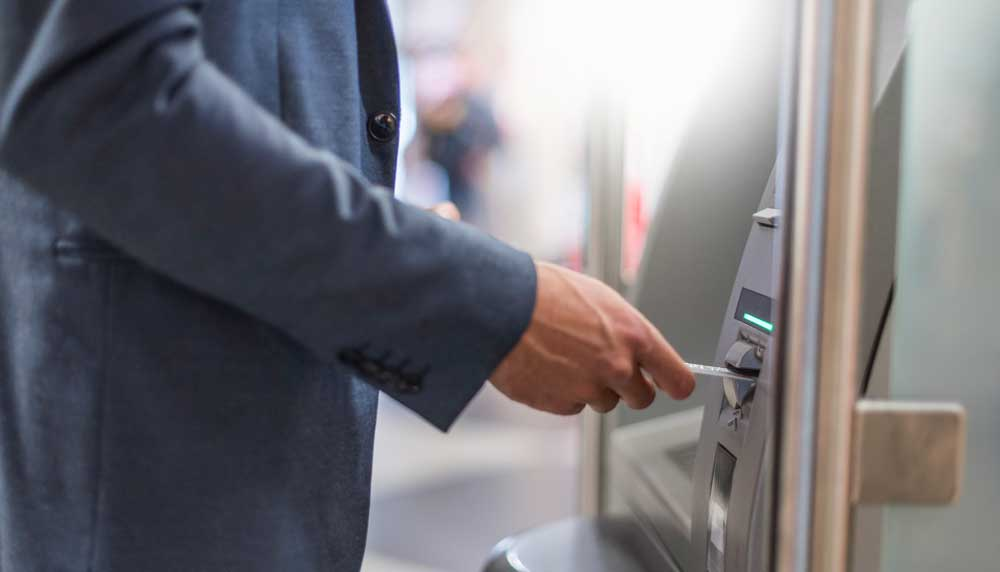 Man at ATM inserting his broadway bank debit card into machine