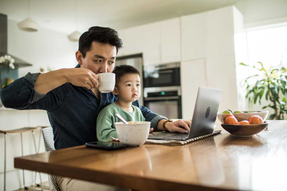 Man sitting with son at kitchen table drink coffee and reviewing computer