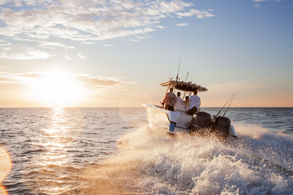 Men enjoying in speedboat at sea against sky during sunset