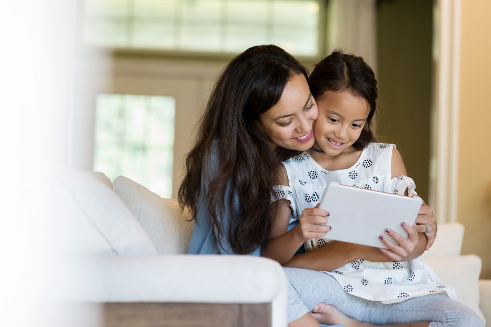 Hispanic mother and daughter looking at tablet