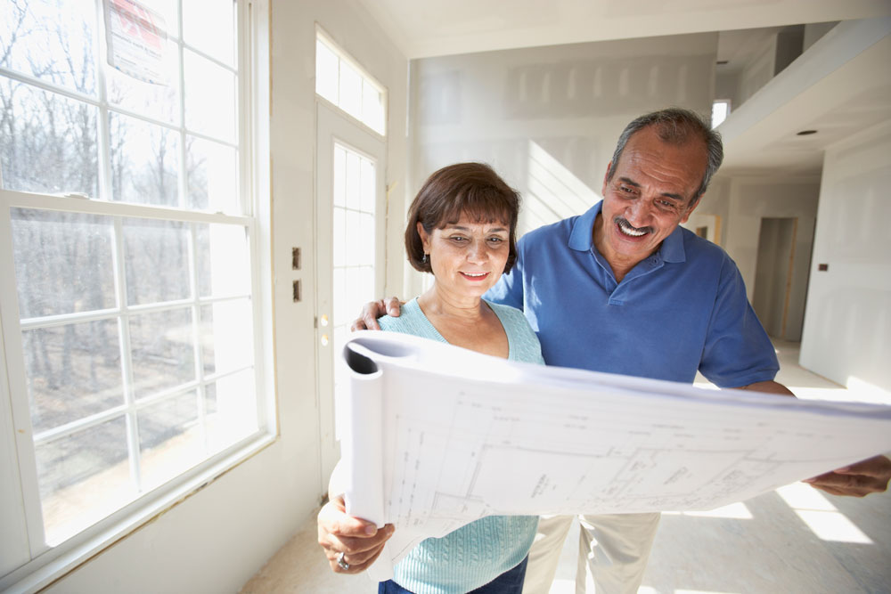 Older couple reviewing floor plans for their custom built home