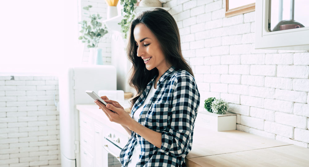 Woman reviewing her overdraft protection on her phone at home