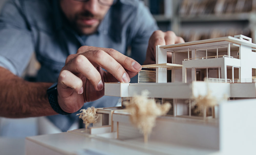 an architect builds a scaled custom home model