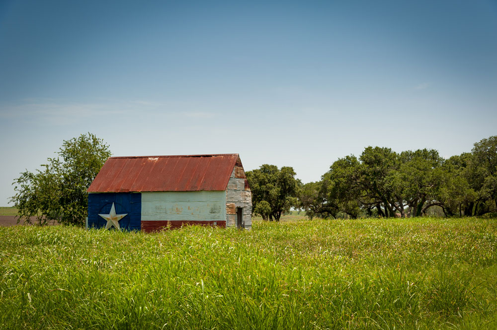 a barn in an open field with a Texas flag painted on the side