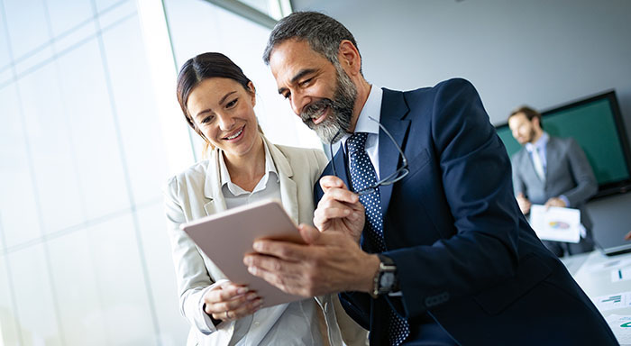 Business woman and business man reviewing Business Savings account info on a tablet