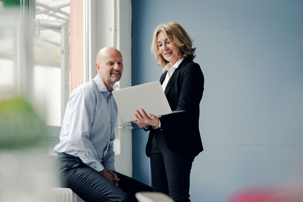 Two business professionals look at a laptop together