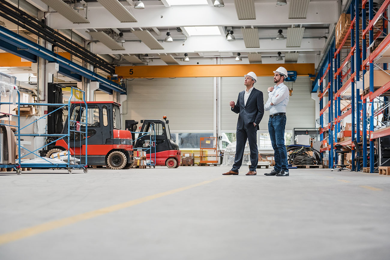 Commercial business owners in a warehouse reviewing inventory