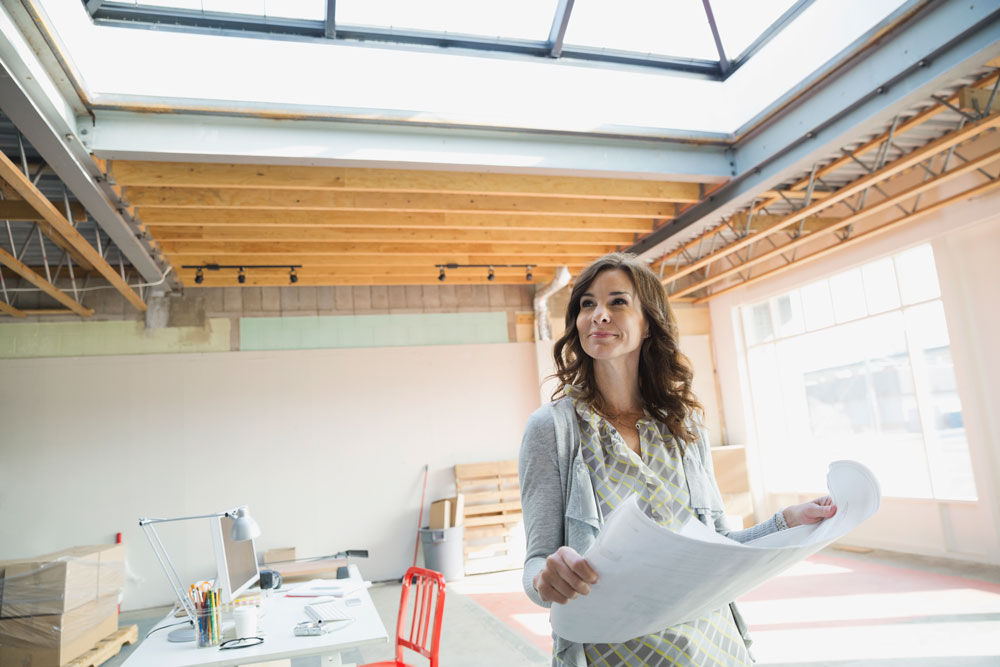 a woman hold blueprints for a new commercial real estate project