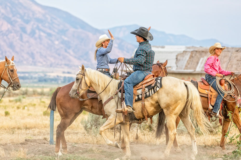 a family rides horses on their ranch together