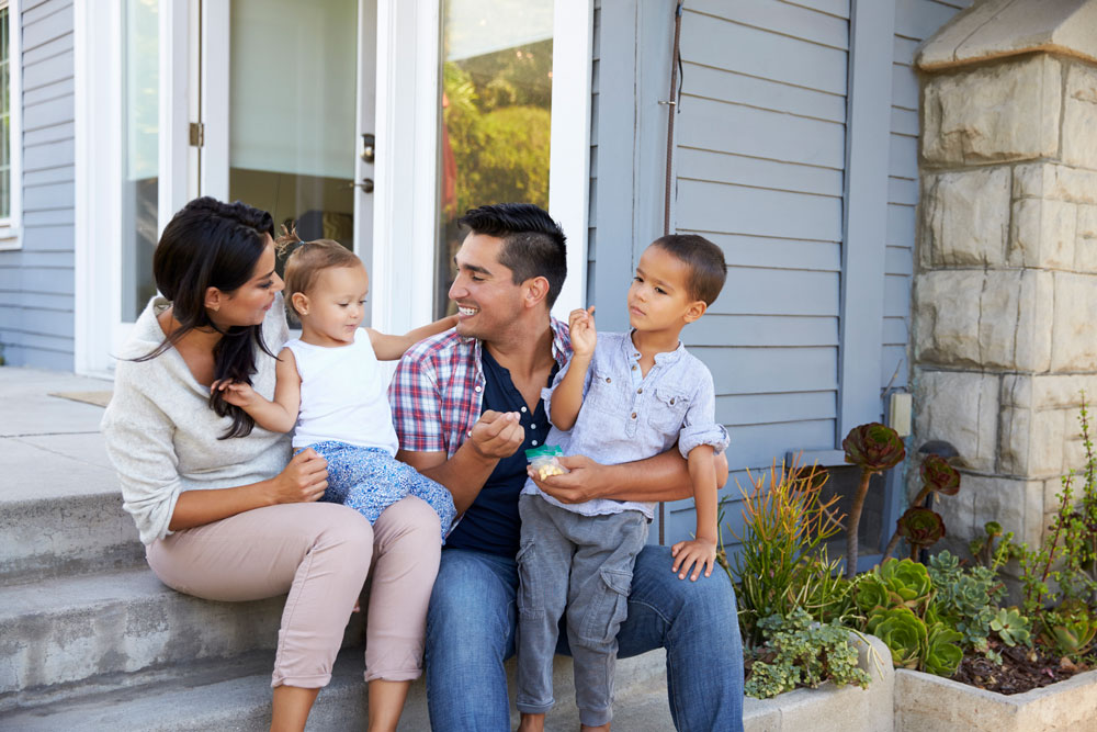 a family sits on the steps of their new home