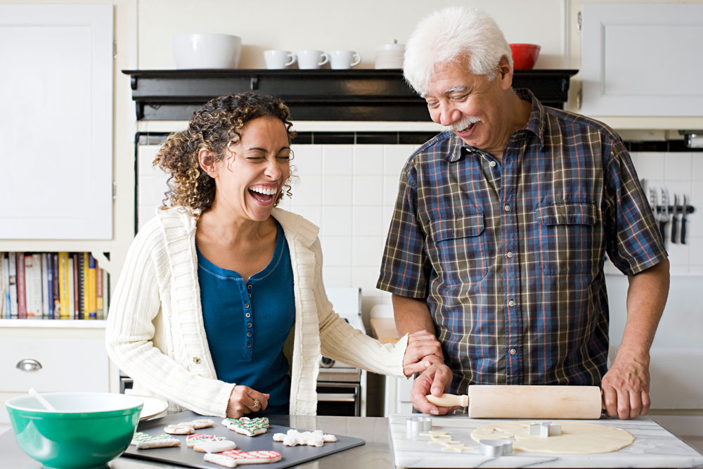 an older father and daughter laugh while baking together