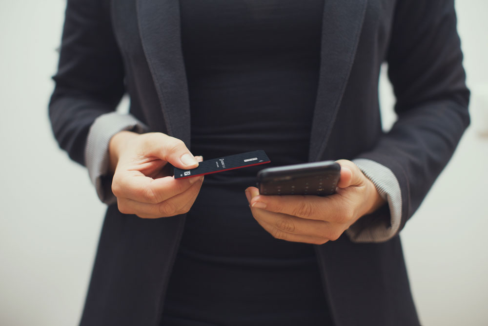 a business woman holds a phone and her Broadway Bank Visa Business Banking debit card