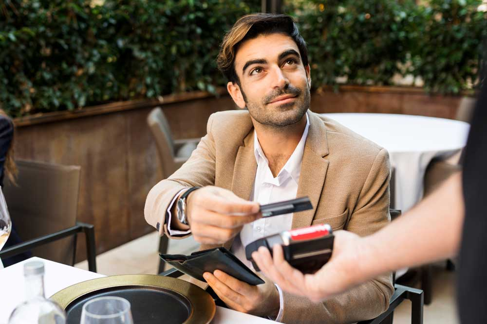 a business man pays his bill with a Broadway Bank commercial credit card