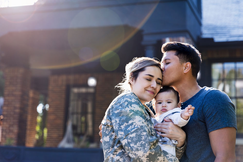 an active military woman hugs her family in front of their new home