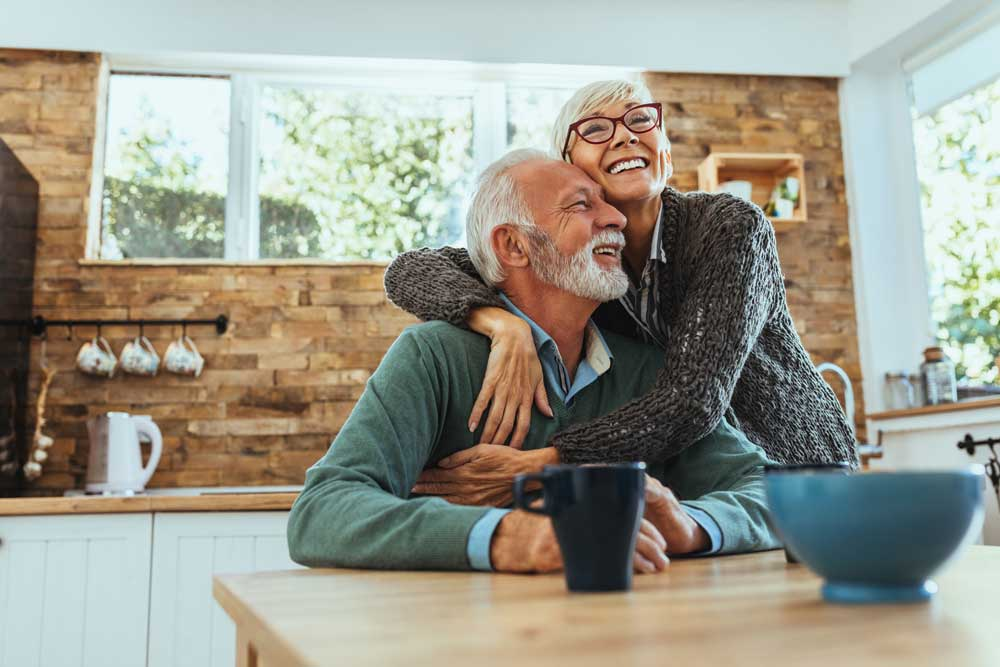 an older couple smiles while hugging each other