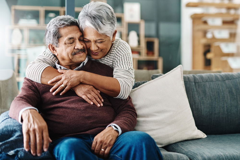 An older hispanic couple shares a hug on the couch