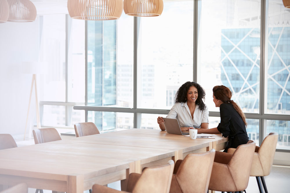 a private banker meets with her client at their office