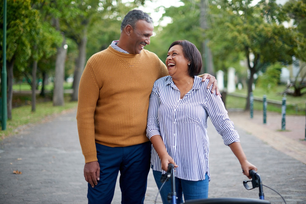 a senior couple walks together in the park