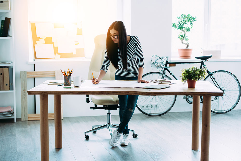 A woman who just applied for a small business working capital loan works at a drafting table