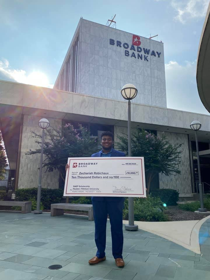 a student receives a scholarship donation from Broadway Bank