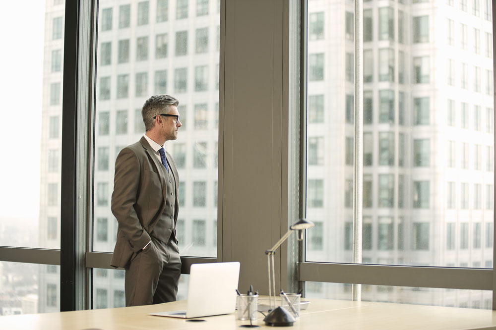 a successful businessman looks out the window of his office