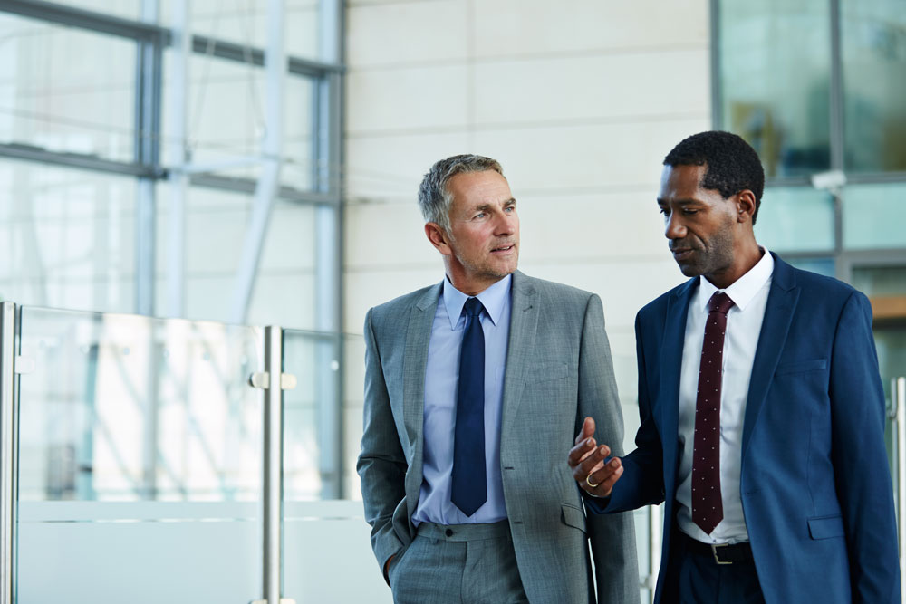 two business professionals talk while walking together