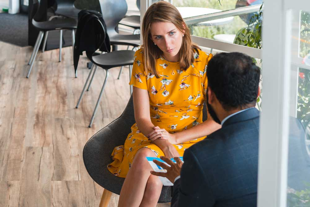 a woman meets with her private banker at her office