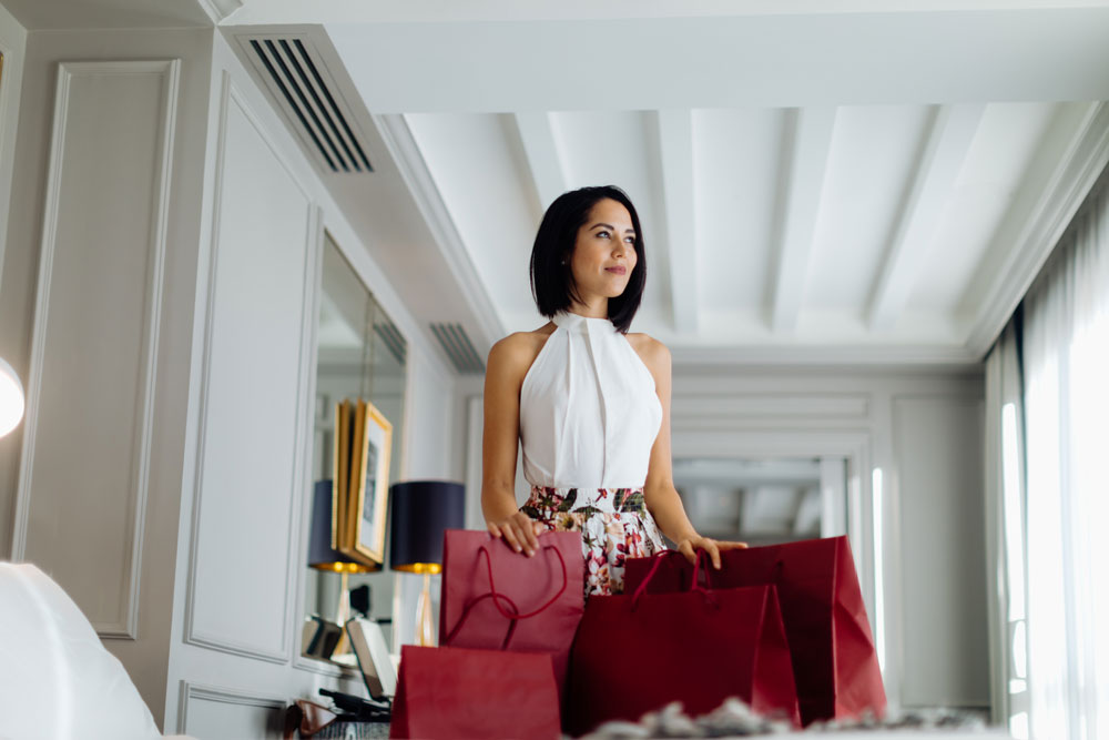 a woman returns from shopping to her elegant home