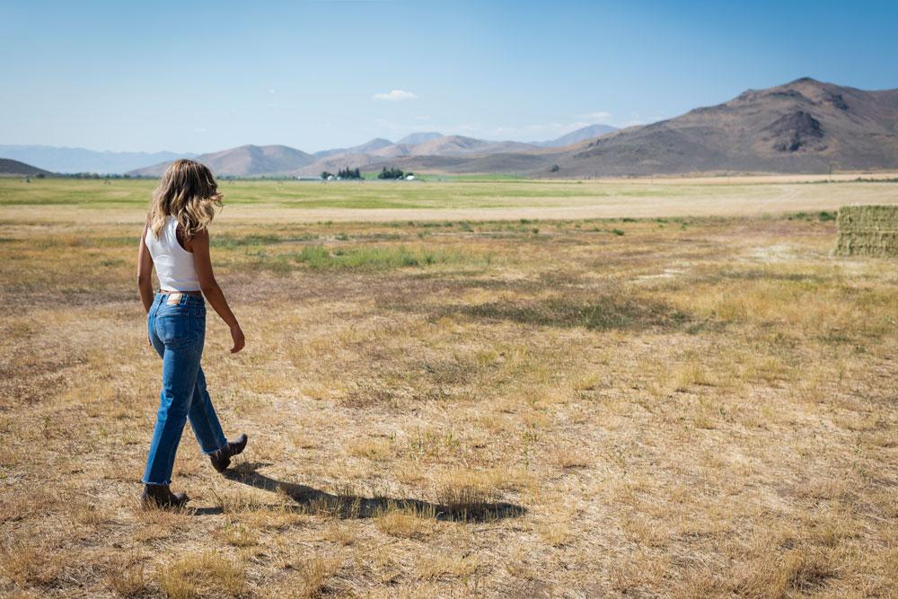 a woman walks through an open field